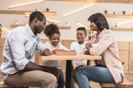 cute african-american family using tablet in cafe Stock Photo