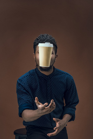 african american man catching disposable coffee cup isolated on brown Stock fotó