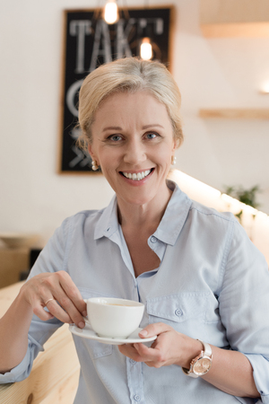 portrait of attractive mature woman drinking coffee and smiling at camera in cafe