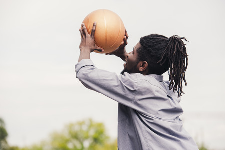 african american man training and throwing basketball ball