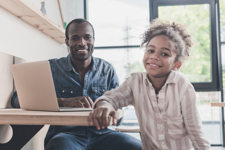 smiling african-american father and daughter sitting in cafe with laptop