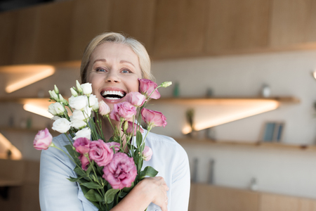 cheerful mature woman holding beautiful flowers and smiling at camera