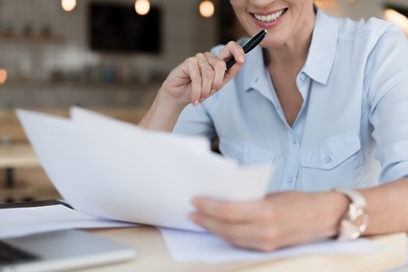 cropped shot of smiling businesswoman working with papers