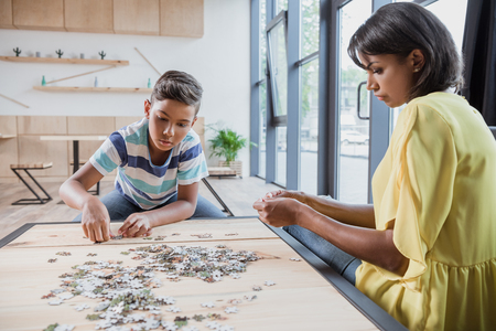 adorable african-american son with mother assembling puzzle 스톡 콘텐츠