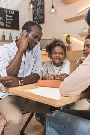 african-american family sitting in cafe while father talking by phone