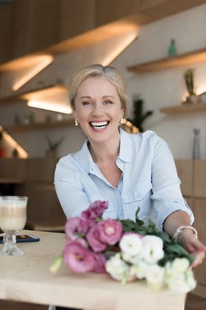 happy mature woman with beautiful flowers sitting at table and smiling at camera in cafe