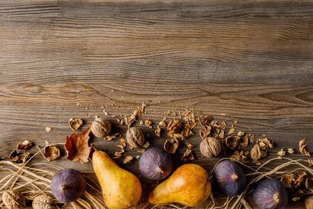 top view of seasonal fruits and walnuts on wooden tabletop