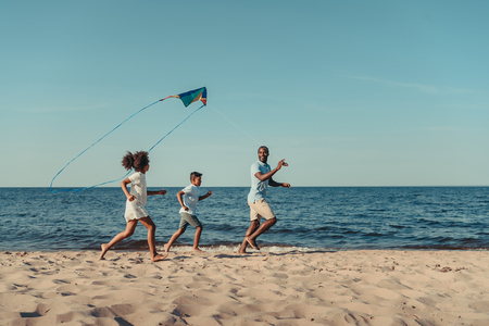 happy african american father and kids playing with kite on beach 스톡 콘텐츠
