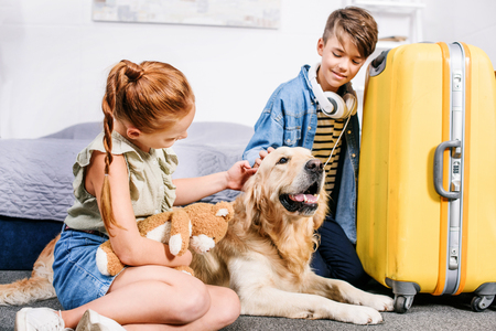 adorable kids petting dog in bedroom with yellow suitcase for trip