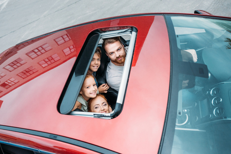 high angle view of family looking out of sunroof of car Stock Photo