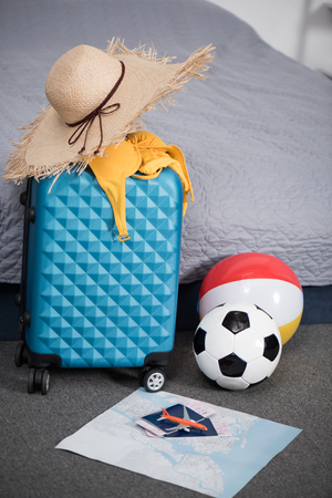 suitcase for trip with straw hat and balls in bedroom Archivio Fotografico - 102256760