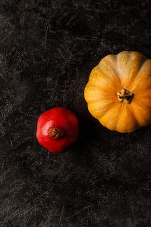 top view of autumnal pomegranate and pumpkin on dark tabletop