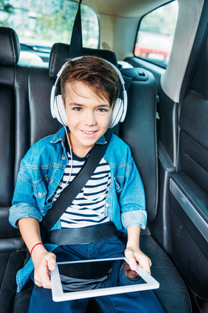 little boy with tablet and headphones listening music in car and looking at camera