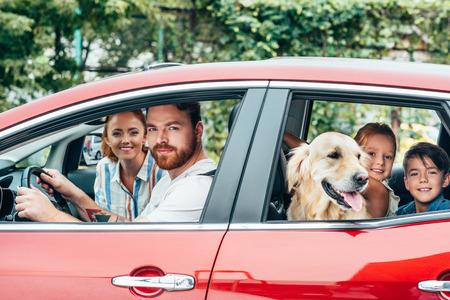Heureuse jeune famille voyageant en voiture avec chien Banque d'images
