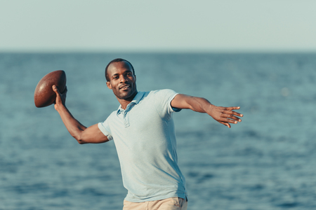 handsome young african american man throwing rugby ball on beach