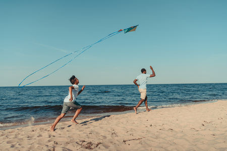 happy african american father and son playing with kite on sandy beach