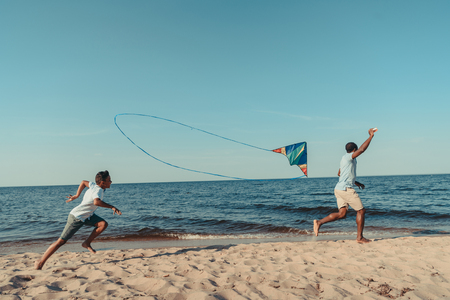 happy african american father and son playing with kite and running on sandy beach