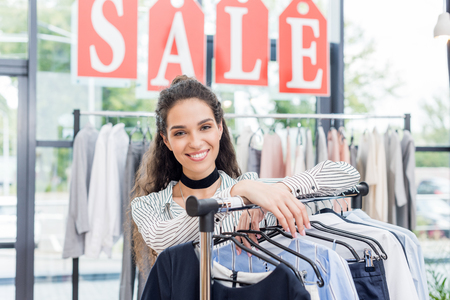 beautiful shopaholic woman leaning on rack in clothes store Stockfoto