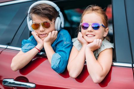 Niños felices en gafas de sol en viaje en coche mirando por la ventana