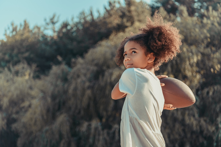 beautiful african american girl throwing rugby ball and looking away