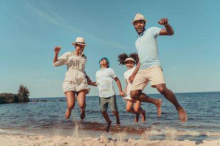 gelukkige Afro-Amerikaanse familie hand in hand en springen op het strand Stockfoto