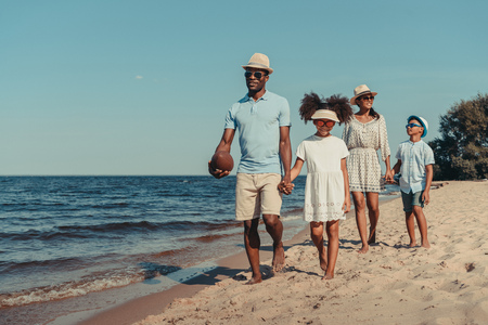 beautiful smiling african american family with rugby ball walking together on sandy beach