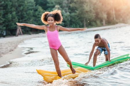happy african american kids having fun with swimming mattresses in sea