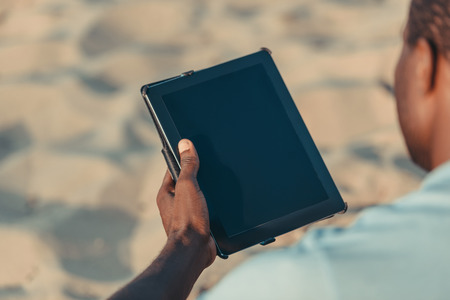 cropped shot of african american man using digital tablet with blank screen