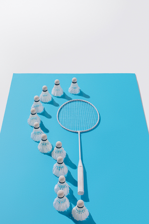 high angle view of badminton racket and shuttlecocks on blue paper, isolated on white