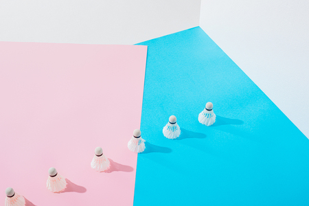 row of badminton shuttlecocks on pink and blue papers Stock Photo
