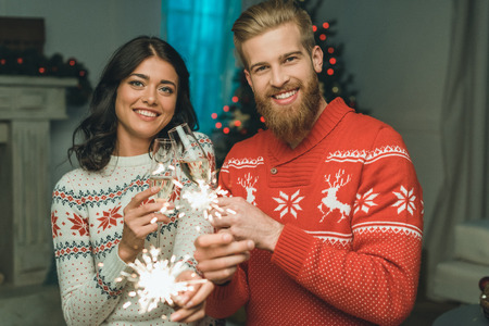happy couple celebrating christmas with champagne and sparkle sticks