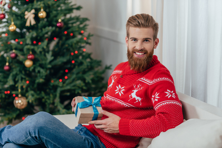 man holding christmas gift and looking at camera