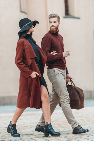 stylish couple walking outdoors in old european city