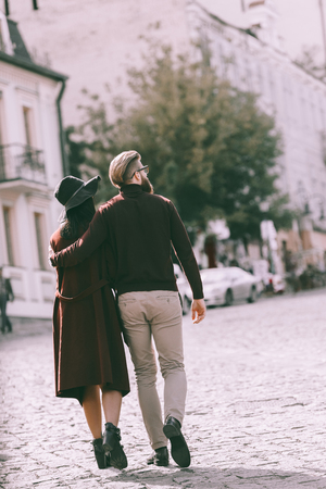 back view of fashionable couple walking at old european city