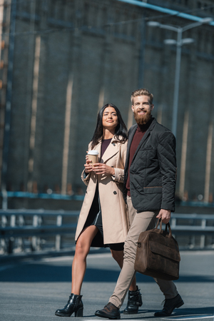 beautiful couple walking outdoors with disposable cup of coffee
