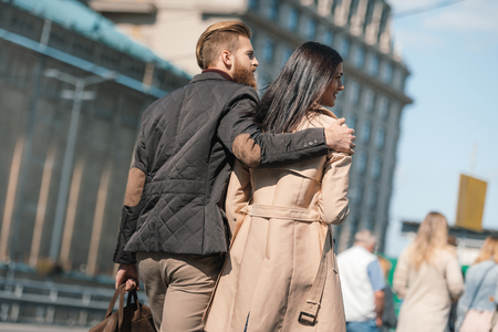 back view of young couple in stylish clothing walking outdoors