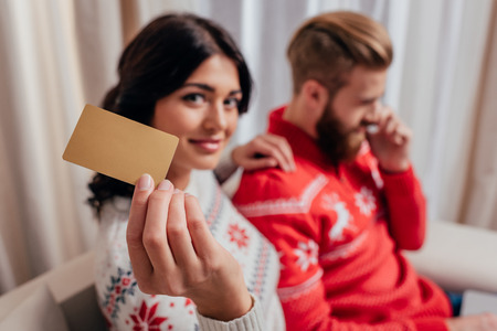woman in winter sweater showing credit card while man talking by phone 版權商用圖片