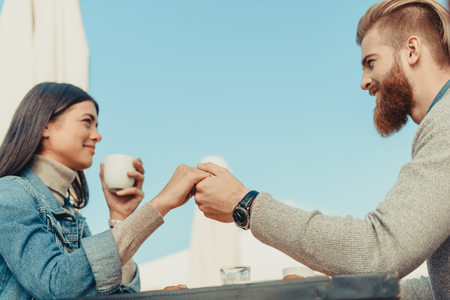young couple holding hands in cafe outdoors Stock Photo