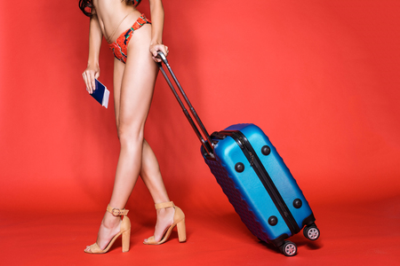 Cropped shot of woman in bright swimsuit and heels, holding a suitcase and airplane tickets