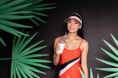 Half-length shot of smiling asian woman in orange swimsuit and visor holding a milkshake and looking at camera 免版税图像