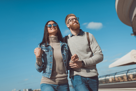 young couple having walk outdoors on sunny autumn day