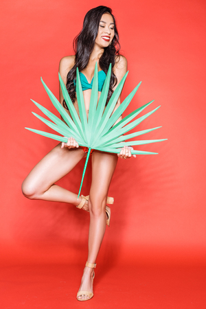 Full-length shot of beautiful asian woman in bright swimsuit posing with palm leaf and looking aside