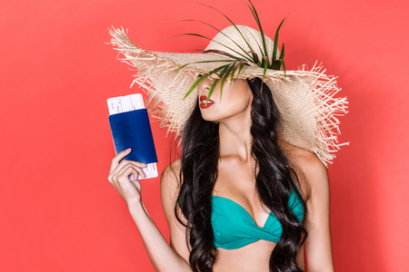 Half-length shot of beautiful asian woman in bright swimsuit and beach hat holding airplane tickets