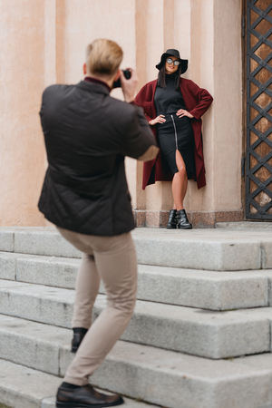 man taking photo of beautiful girlfriend next to ancient building with vintage camera