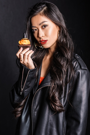beautiful asian woman in leather jacket with cupcake in her hand, looking at camera Stock Photo