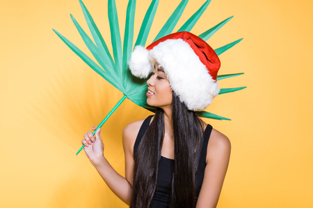 smiling asian woman in black swimsuit and santa hat holding a fake palm tree leaf
