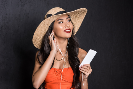 89fc8e1156 beautiful asian woman in beach attire listening to music in earbuds and  holding a smartphone