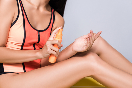 Cropped shot of beautiful asian woman in coral swimsuit, applying sunscreen lotion on hand