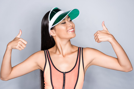 Half-length shot of happy asian woman in coral swimsuit and visor showing thumbs up and looking aside