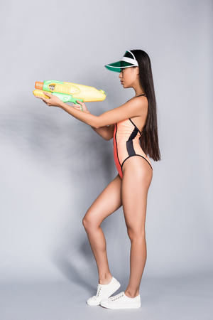 Side view shot of beautiful asian woman in coral swimsuit and visor posing with a water gun